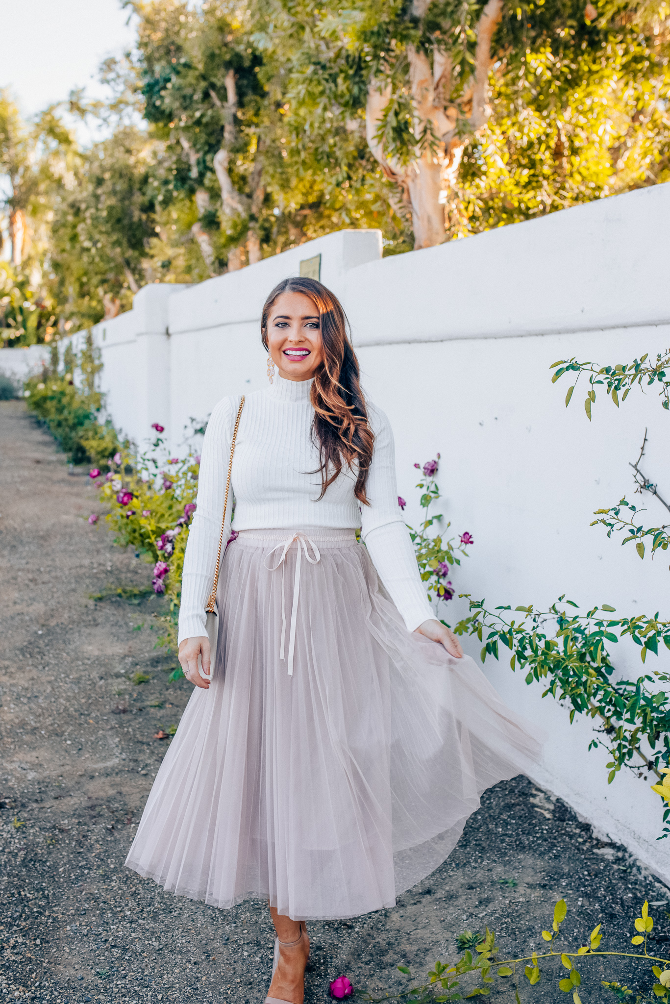 Tips to style a layered tulle skirt featured y top Los Angeles fashion blogger, Maxie Elise: image of a woman wearing a Chicwish long tulle skirt, Forever 21 cream turtleneck, Lisi Lerch earrings and Steve Madden sandals