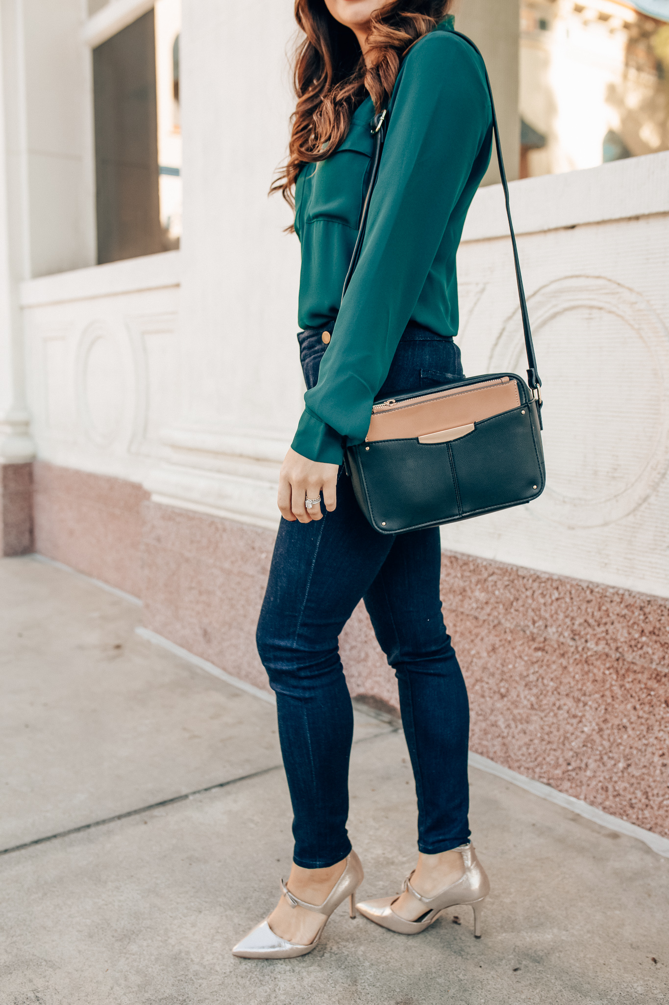Winter workwear featured by top Orange County fashion blogger, Maxie Elise: image of a woman wearing an Ann Taylor green slim shirt, Ann Taylor skinny jeans, Ann Taylor metallic leather pumps and Ann Taylor camera bag