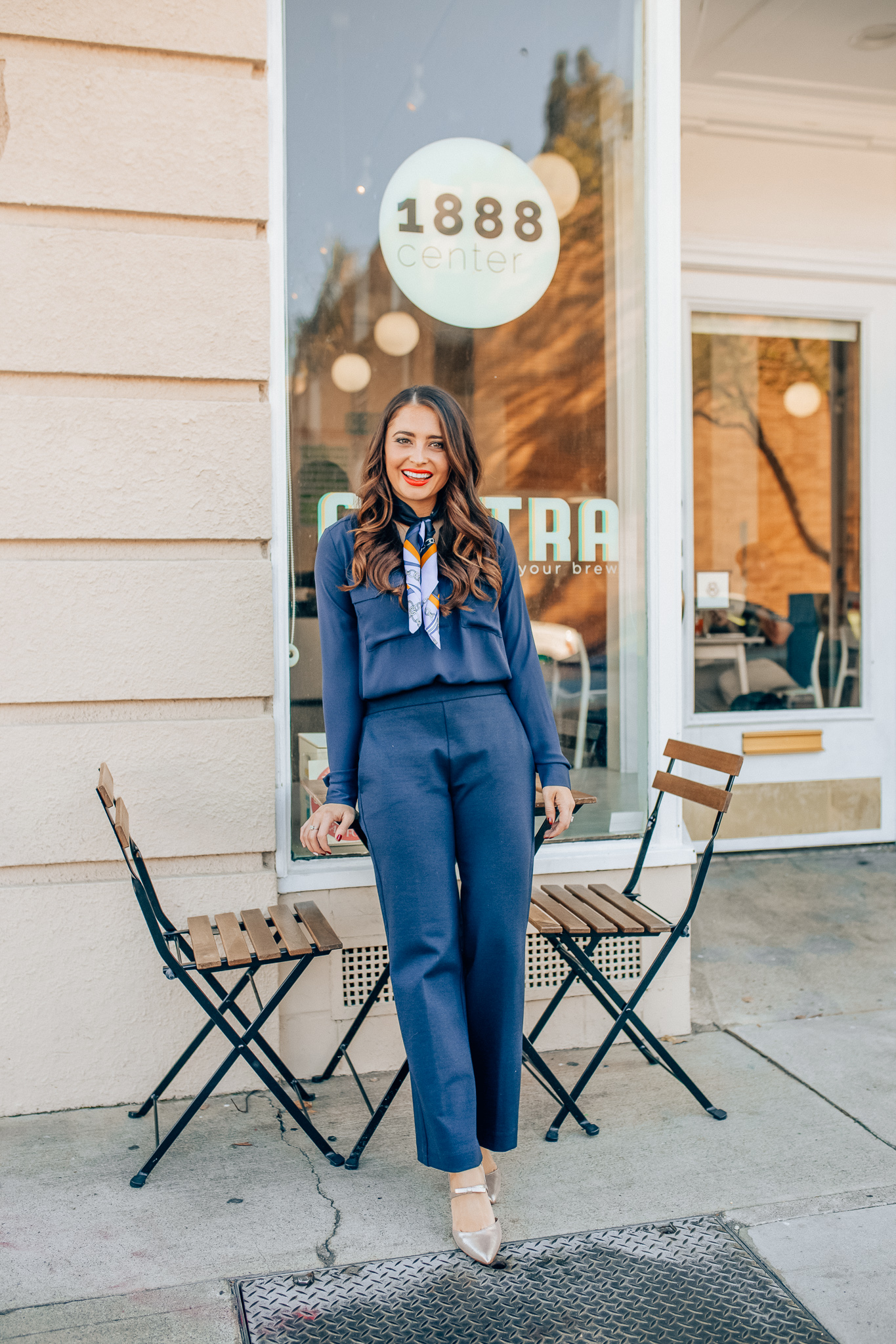 Winter workwear featured by top Orange County fashion blogger, Maxie Elise: image of a woman wearing an Ann Taylor blue slim shirt, Ann Taylor wide leg pants, Ann Taylor silk scarf, Ann Taylor metallic leather pumps and Ann Taylor camera bag