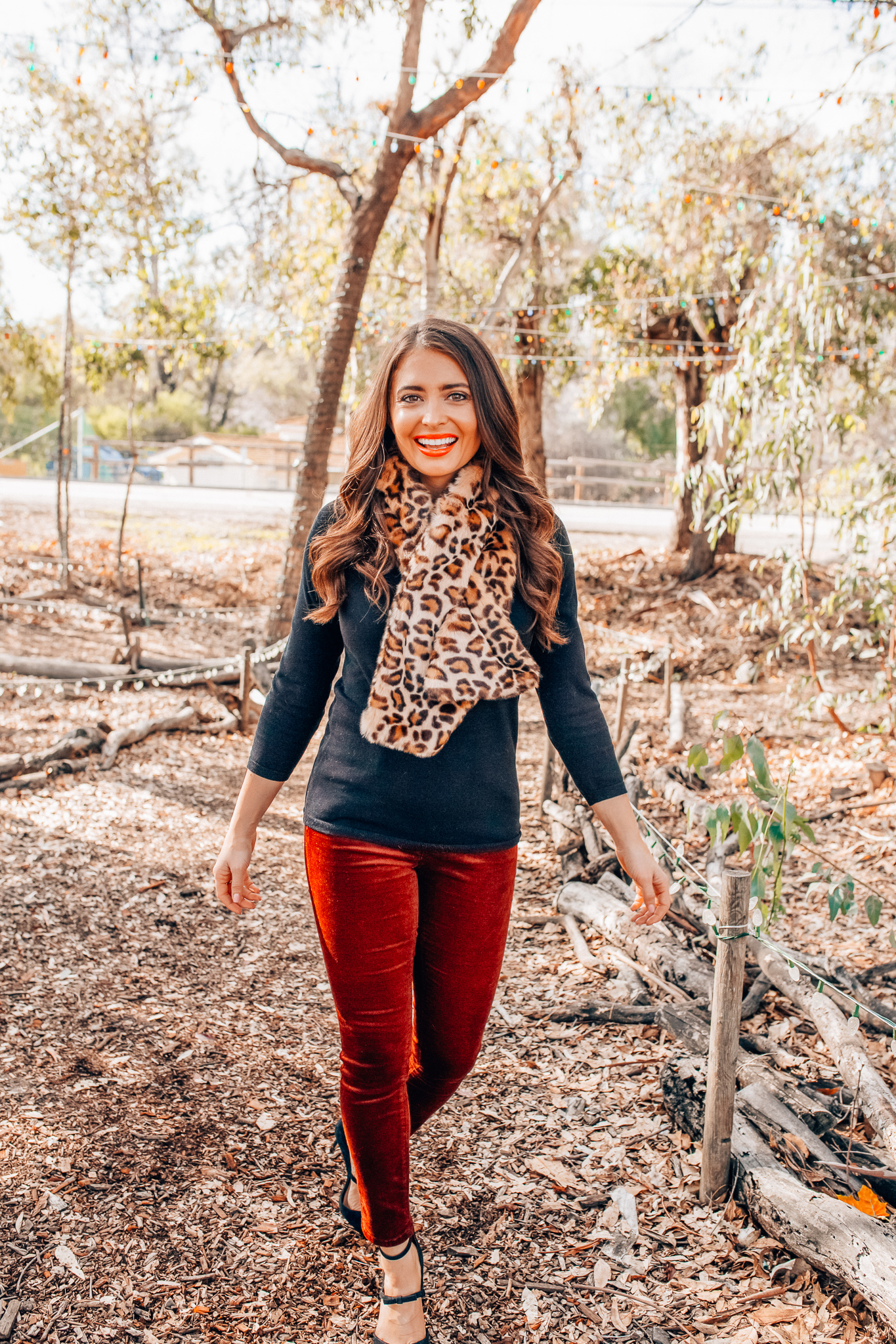 Leopard Holiday style featured by top Orange County fashion blogger, Maxie Elle: image of a woman wearing an Ann Taylor 3/4 sleeve black sweater, Ann Taylor faux fur stole, Ann Taylor red velvet pants, and Ann Taylor suede bow pumps