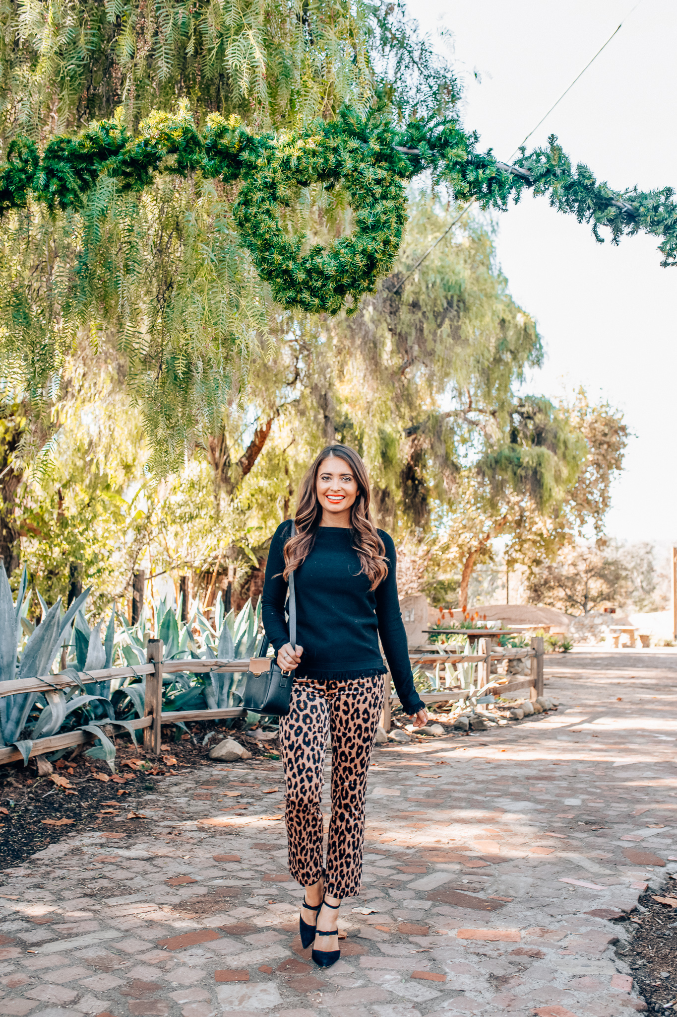 Leopard Holiday style featured by top Orange County fashion blogger, Maxie Elle: image of a woman wearing an Ann Taylor black fringe sweater,  Ann Taylor leopard velvet pants, and Ann Taylor camera bag