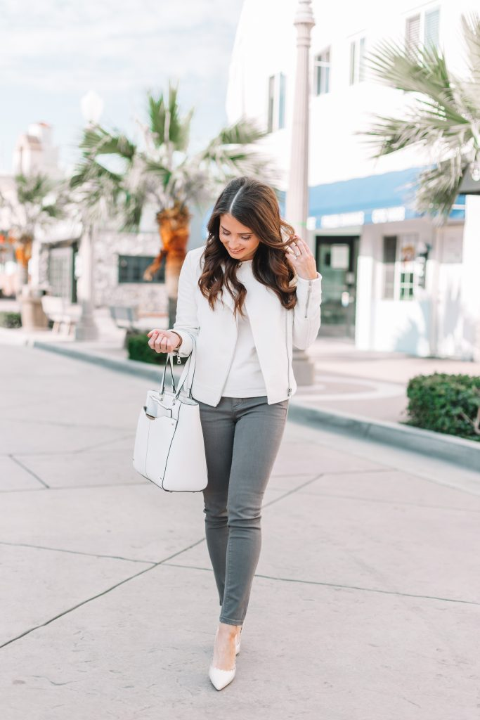 brunette woman in spring jacket and grey jeans standing in street