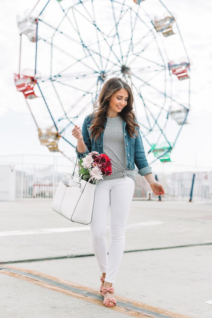 brunette woman in spring jacket and white jeans standing in front of ferris wheel