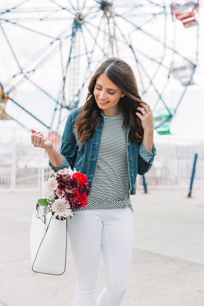 Brunette woman in spring jacket holding flowers