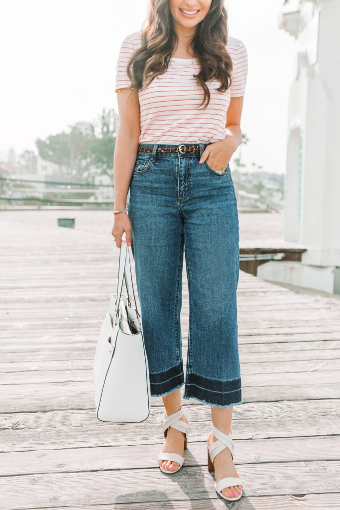 woman wearing wide leg cropped denim and holding white bag