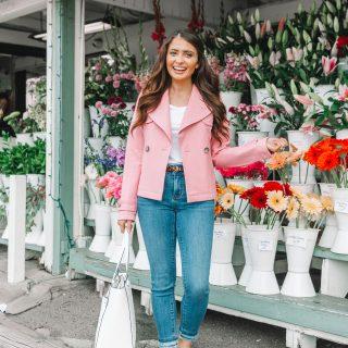 brunette girl in front of flower shop in pink coat