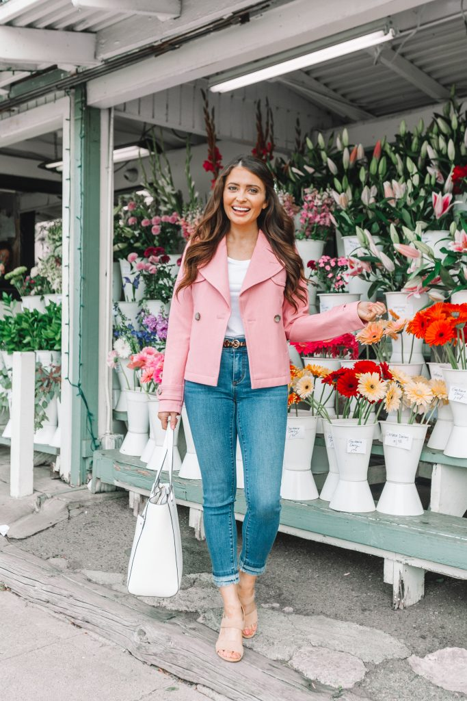 brunette girl in front of flower shop in pink coat