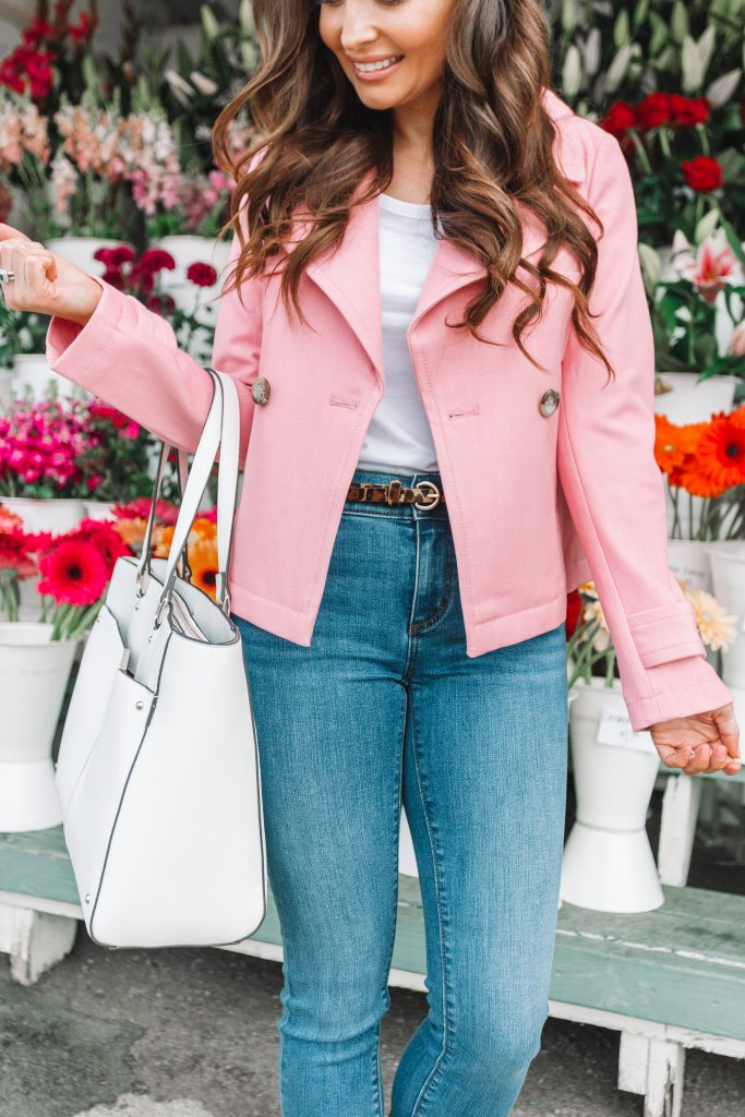 girl holding white bag wearing pink jacket and jeans