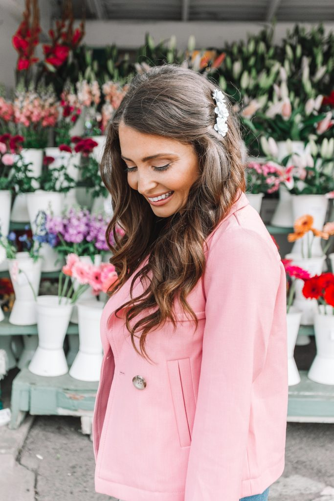 brunette girl with flower barrette and pink jacket